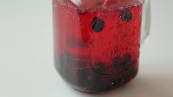 Schritt für Schritt Zubereitung von Cocktails mit Zitrone und Orange. Hinzufügen von Beeren und Eis zu kohlensäurehaltigem Wasser.