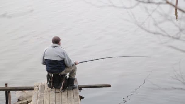 Rybář sedí na molu s rybářskou tyčinkou. Rybaření na jezeře, minimalismus.