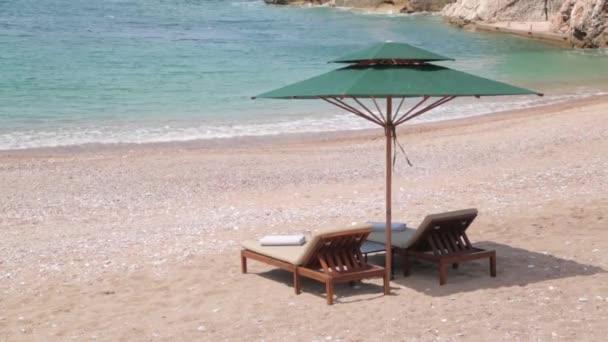 Malebné pobřeží nedaleko ostrova Sveti Stefan. Turistická pláž s pískem a lehátky v Černé hoře.