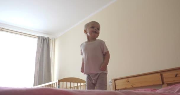 Egy kisfiú (gyermek) nagyon örömteli Ugrás a kanapén teljes növekedés. A koncepció: vidám Baby, egészséges gyermek, mosoly, nevetés, Joy of Life.