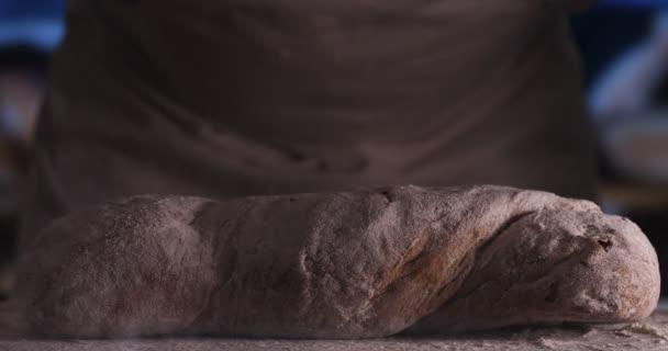 A pékség, a Pék sütés után friss kenyér Sprinkles cukor por (Liszt) a kenyér (Liszt tészta), a por szűrőedény (kézzel). Koncepció: friss kenyér, házi készítésű, a kezek, lassított.