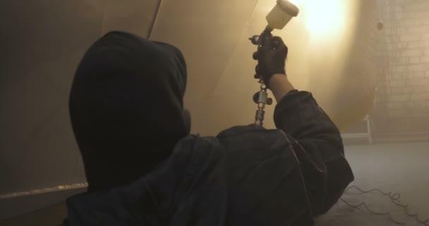 V pomalém pohybu profesionální muž (muž) v garáži (služba) v pracovních šatech oblečených ve svetru vytvoří stříkací pistoli (sprej) a začne malovat (vložením keramických vrstev) jachty.