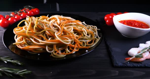 Vařené jídlo doma (v restauraci) kuchař zdobí hotovou těstovinovou mísu strouhaným parmazánem na kuchyňském strouhanci a přidává omáčku. Koncept: Sýr, Nádherné jídlo, Zpomalený pohyb.