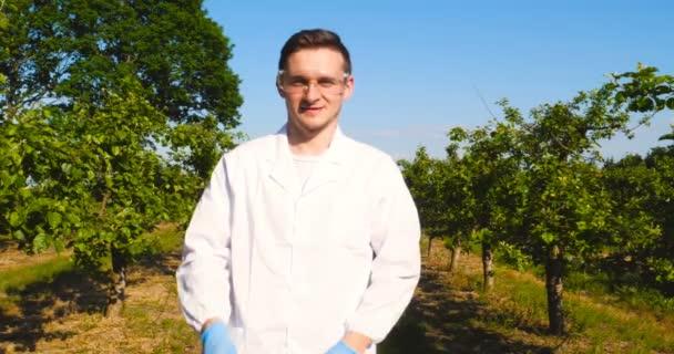 ein junger schöner (männlicher) Biologe oder Agronom, nimmt Analysen von Feuchtigkeitsblättern vor, dna, Pipette, in weißem Mantel, Brille, blauen Gummihandschuhen, geht über den Apfelbaum. Schöner Biologe oder Agronom in weißer medizinischer Kleidung, Schutzbrille.