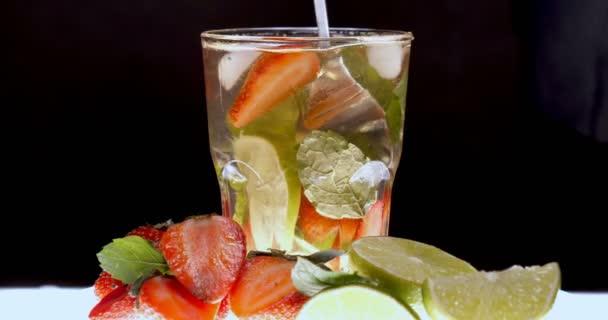Der Barmann (Barkeeper) bereitet verschiedene Getränke (Cocktails) für eine Party zu. in der Bar in der Disco oder zu Hause, kalte Fruchtgetränke sind auf schwarzem Hintergrund zu sehen.