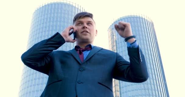 Mladý muž (muž) architekt, podnikatel v pracovním obleku, v bundě se složkou s tabletem (mobilní telefon) v ruce kontroluje staveniště a obchodní budovy pomocí různých akcí.
