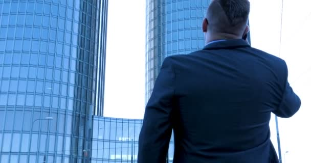 Ein junger Mann (männlich) Architekt, ein Geschäftsmann im Arbeitsanzug, in einer Jacke mit einem Ordner mit einem Tablet (Handy) in der Hand überprüft die Baustelle und das Geschäftshaus mit verschiedenen Aktionen.