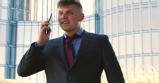 A young guy (male) architect, a businessman in a working suit, in a jacket with a folder with a tablet (mobile phone) in his hands checks the construction site and business building using various actions.