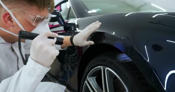 Profesionální muž (chlapec) mistr keramiky vozu klade keramiku na auto pomocí vlákno (houba) hadr v tahač, bezpečnostní brýle a černé rukavice a kompletně kontroluje auto po lakování (diagnostika) na chyby (škrábance) a složení barvy