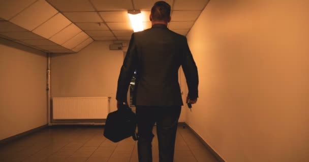 Young handsome guy (man) businessman standing (sitting) by a tree in a suit.  Climbs the stairs with a black bag in his hands. Concept: business, suit, guy, man, bag, businessman.