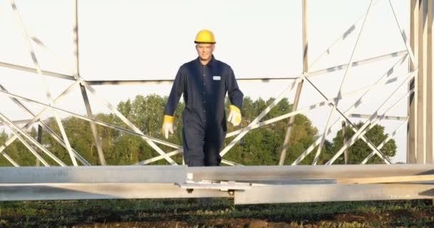 ein Elektriker oder Bauarbeiter und Ingenieur, in blauem Gewand, mit gelb-weißem Helm, überprüft die technische Übersicht auf Festigkeit, bereitet Strommasten, einen Strommast, Energie und Arbeiter vor.