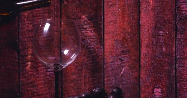 Az asztalon van egy kristály üveg, egy üveg vörösbor, sajt, fekete lemez, a háttérben egy bár pult.