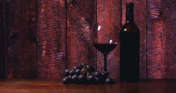 Na stole je Křišťálová sklenička, láhev červeného vína, sýr v černé desce, pozadí baru.