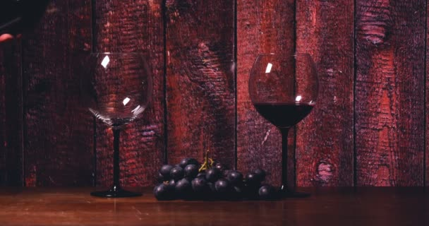 On the table there is a crystal glass, a bottle of red wine, cheese in a black plate, a background of a bar counter.