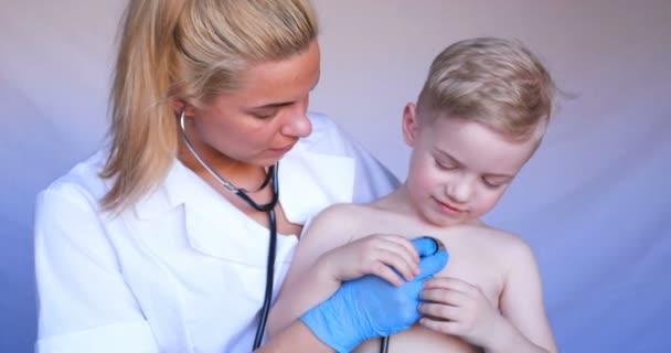 eine junge Krankenschwester hört sich die Lungen eines Kindes mit einem Stethoskop an, überprüft dann die Ohren und die Temperatur des Patienten, nimmt dann die Maske ab und überprüft die Vorgeräte, im Krankenhaus, in der Poliklinik (zu Hause) den Arzt, schnell.
