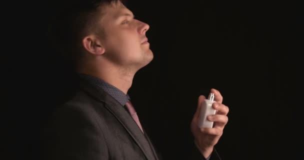 Mladý chlapík (muž) je Dusen parfémem, na černém pozadí v košili. Pojem: parfémy, košile, sprej, fešák, muž, krása, černé pozadí, styl.