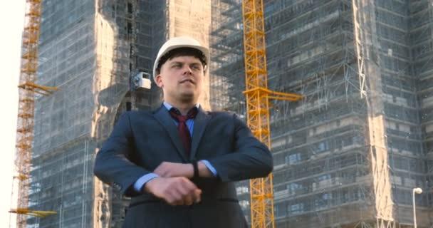 Portrét úspěšného mladého pohledného inženýra, architekta, stavitele, obchodníka, v bílé přilbě, v obleku, s poznámkovým blokem, mrakodrapem a budovou.