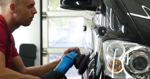 A professzionális karosszéria és fényszóró polírozó munkavállaló szállítja az autót festés után, vagy készül az eladásra. Koncepciója: Frissítő autók, Autóipari központ, Szerviz, Professzionális.