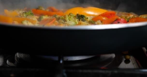 Lahodná čerstvá zelenina je dušená v pánvi, jídla pro vegetariány doma. Koncepce: VEG, bio produkt, houby, brokolice, barevné zelí, mrkev, kukuřice, paprika.