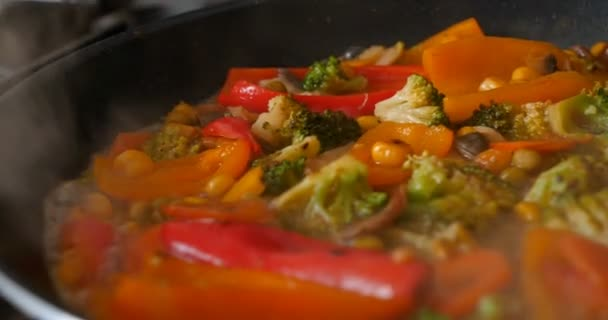 Delicious fresh vegetables are stewed in a pan, food for vegetarians at home. Concept of: Veg, Bio Product, Mushrooms, Broccoli, Colored Cabbage, Carrot, Corn, Paprika.