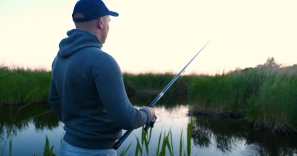 Egy ember a természet a halászat nyugszik, dobja a csalit a folyóba, bekapcsolja a tekercset, és emelje fel a csali a csúcsra. Fogalma: horgászat, nyaralás, üdülés, Relax, folyó, tó, lassított, Clean Air.