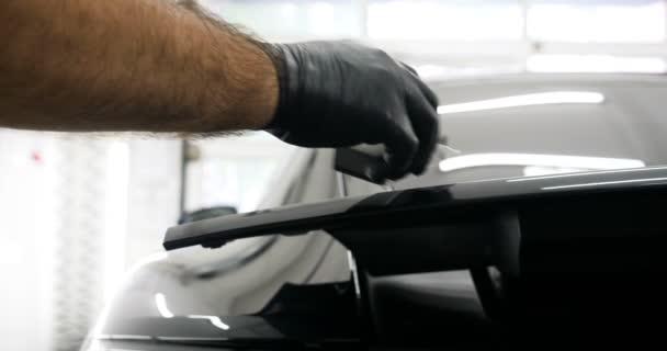 Mitarbeiter tragen bei der Arbeit chemische Schutzkleidung. Automobilindustrie. Autowaschanlage und Beschichtung Geschäft mit Keramikbeschichtung. Spritzen der Lack auf das Auto. Konzept von: Schutz des Autos, Service, Glanz.
