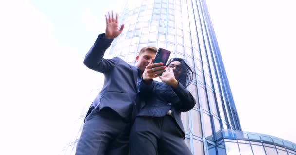 Fun Young Couple Taking Selfie With Mobile Phone on skyscraper background. Concept of: Suite, Business, Couple, Architecture, Smartphone, Lifestyle, 5g network.