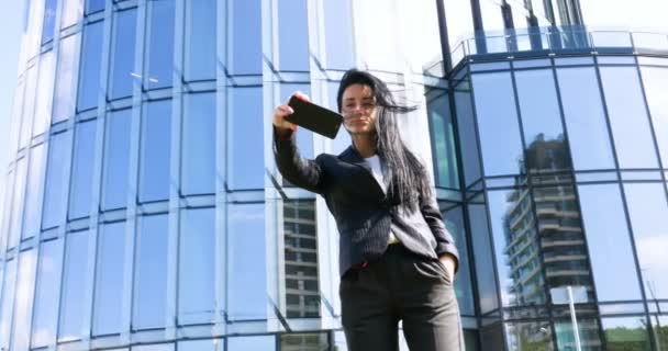 Businesswoman making selfies in front of office building. Smiling lady taking photos for her business partners abroad. Concept of: Lifestyle, Mobile, Selfie, Alone, Summer.