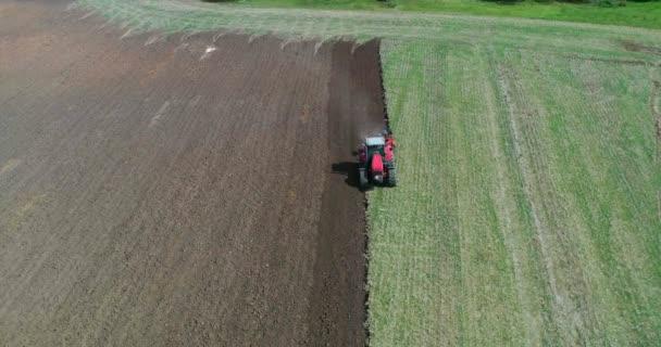 Letecký pohled dron pole sklizně s traktorem seká suchou trávu. Podzimní žluté pole s kupkou sena po výhledu shora. Harves. Ting in the fields. Zásoby nahoru