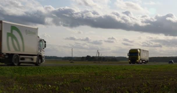 Asfaltová cesta na pampeliškovém poli s malým náklaďákem. kamion jede za slunečného večera.