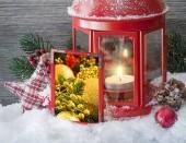 Zimní kompozice s lucernou, sněhem a slavnostními hračkami, obraz v rámečku na popředí.