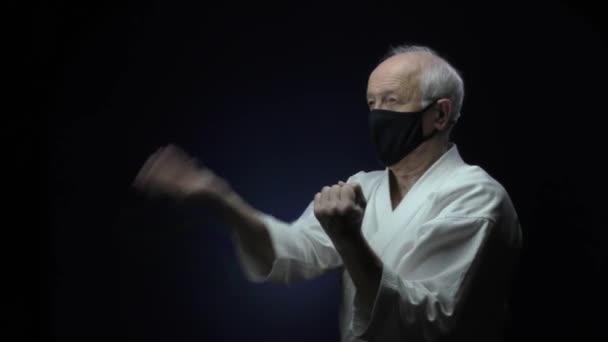 In schwarzer medizinischer Maske trainiert ein alter Athlet vor dunklem Hintergrund