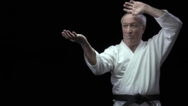 Auf schwarzem Hintergrund trainiert ein alter Athlet formale Karate-Übungen