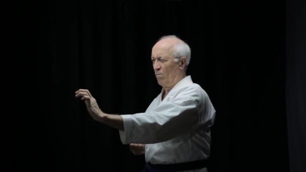 Auf schwarzem Hintergrund in Karategi trainiert ein alter Athlet Schläge und Blöcke mit den Händen