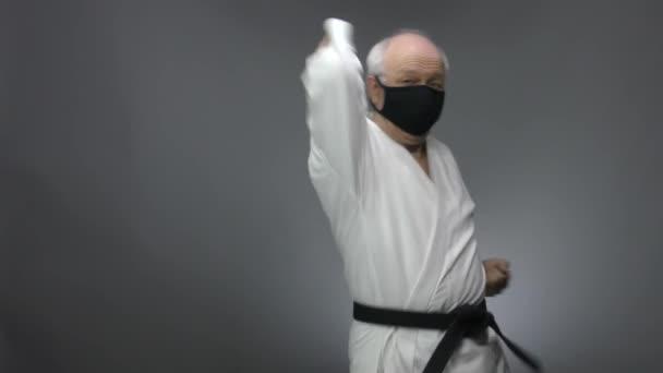 Szürke alapon, egy öreg férfi sportoló fekete orvosi maszkban veri a könyökét.