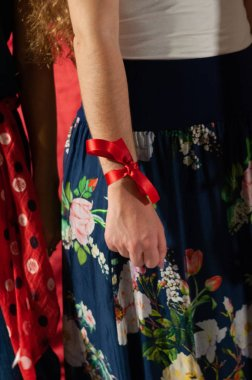 Detail of a young woman's arm with a red ribbon on her wrist against violence against women. Manifestation to stop femicide.