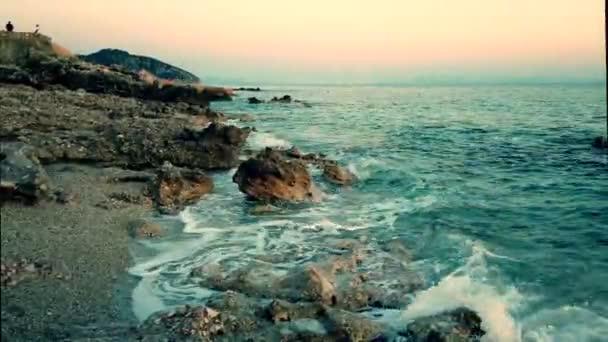 Skalnatá pláž a křišťálově tyrkysová voda v Albánii. Klidný a uklidňující pohled