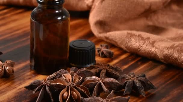 Star Anise essential oil and herbs on a wooden table