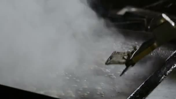 Cleaning a cooking grill in a commercial kitchen