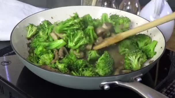 Stirring beef and broccoli with mushrooms in a skillet