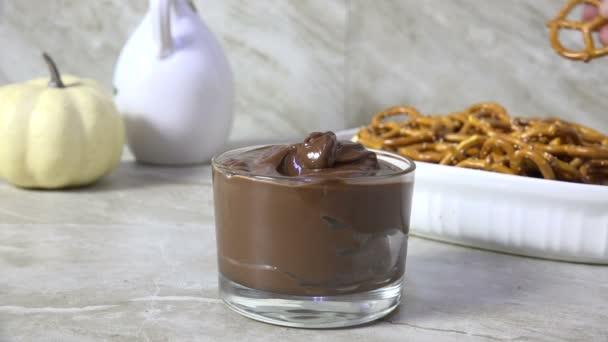 eine gesalzene Brezel in geschmolzene Milchschokolade tauchen