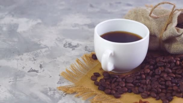 Coffee cup and coffee beans. A white cup of evaporating coffee on the table with roasted bean.