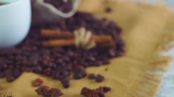 Šálek kávy a kávových zrn. Bílý hrnek odpařovací kávu na stůl s pečené fazole.