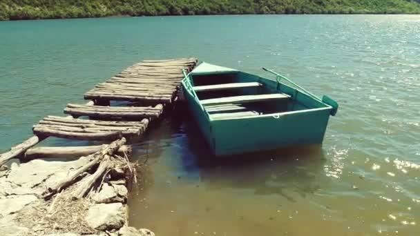 Ein einsames Boot liegt am Holzsteg vor Anker.