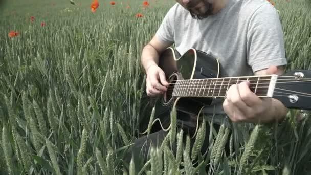 Férfi játszik területén kívül fekete akusztikus gitár.
