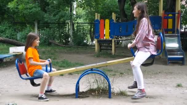 Happy dvě děti jezdit na houpačce na letní park