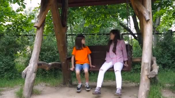 Glückliche zwei Kinder fahren auf einer Schaukel im Sommerpark.