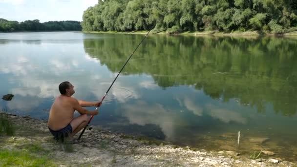 Horgászat a folyó. A halász a folyóparton Horgászbottal.