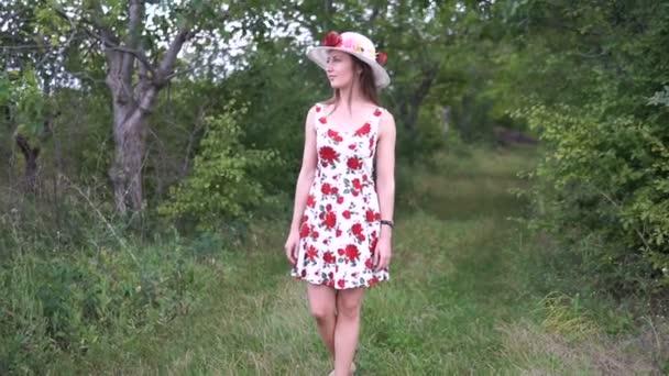 Porträt einer schönen eleganten Frau in hellweißem Kleid und Hut, die im Sommerpark steht.