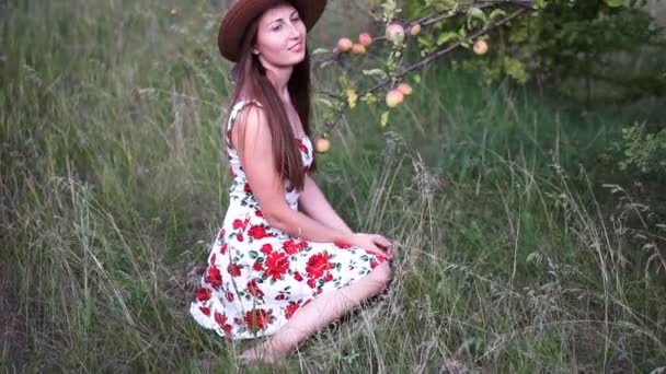 Beautiful blonde girl in hat and dress stands on the apple garden.